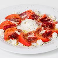 Ensalada de tomate con queso mozzarella, queso feta y jamón ibérico